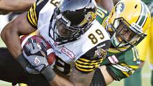Hamilton Tiger-Cats' Onrea Jones (89) is tackled by Edmonton Eskimos' Donovan Alexander (10) during first half action in Edmonton, Alta., on Friday August 2, 2013. (JASON FRANSON/THE CANADIAN PRESS)
