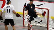 Goalie Carey Price, right, from Anahim Lake, B.C., has the ball tipped under his leg by Jordan Staal, from Thunder Bay, Ont., during a ball hockey training session at the Canadian national men's team orientation camp in Calgary, Alta., Tuesday, Aug. 27, 2013. (Jeff McIntosh/THE CANADIAN PRESS)