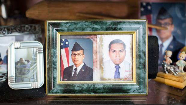 A picture of Agustin Meza, right, is shown beside his younger brother, Raymond Quintero, who is a U.S. soldier.