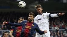 "Real Madrid's Sergio Ramos (R) heads the ball to score a goal as he is challenged by Barcelona's Gerard Pique during their Spanish first division ""classic"" match at the Santiago Bernabeu stadium in Madrid March 2, 2013. (PAUL HANNA/REUTERS)"