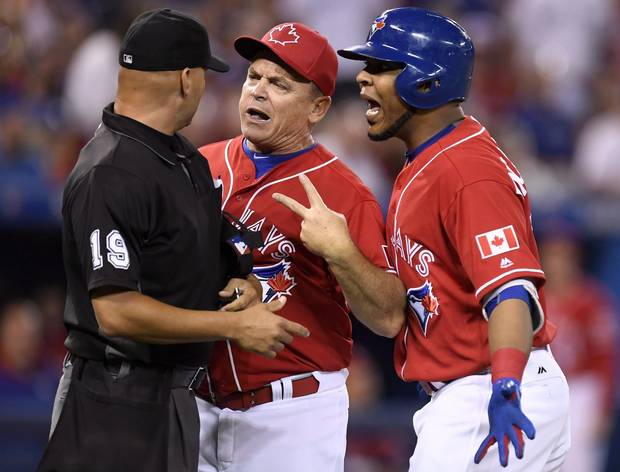 Toronto Blue Jays manager John Gibbons, centre, and designated hitter Edwin Encarnacion exchange words with umpire Vic Carapazza (19) after Encarnacion was ejected from the game over a call-out on strikes during first inning MLB baseball action, in Toronto on Canada Day, Friday, July 1, 2016. The confrontation resulted in Gibbons also getting ejected from the game.
