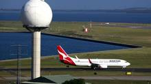A Qantas Airways plane passes a radar tower after landing at Sydney Airport April 29, 2013. (DAVID GRAY/REUTERS)