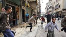 People run upon hearing a nearby plane bombing during a protest against Syrian President Bashar al-Assad in the al-Katerji Tariq district in Aleppo February 22, 2013. (MUZAFFAR SALMAN/REUTERS)