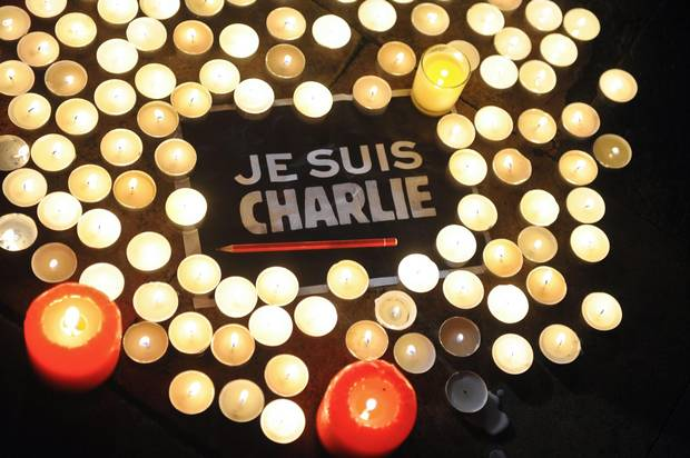 Candles are placed next to a sign reading 'Je suis Charlie' (I am Charlie) and a pen in La Rochelle, France, on Jan. 7, 2015, after the attack by armed gunmen on the offices of French satirical newspaper Charlie Hebdo in Paris.