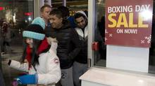 Shoppers push through the door of Future Shop for its 6 a.m. Boxing Day sale in Toronto. (Frank Gunn/The Canadian Press)