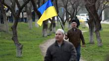 A Crimean Tatar man walks with a Ukrainian flag during a pro-Ukrainian rally in Bakhchisaray March 14, 2014. (DAVID MDZINARISHVILI/REUTERS)