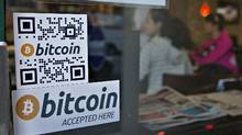 Signs on window advertise bitcoin ATM machine that has been installed in a Waves Coffee House in Vancouver. (Andy Clark/Reuters)
