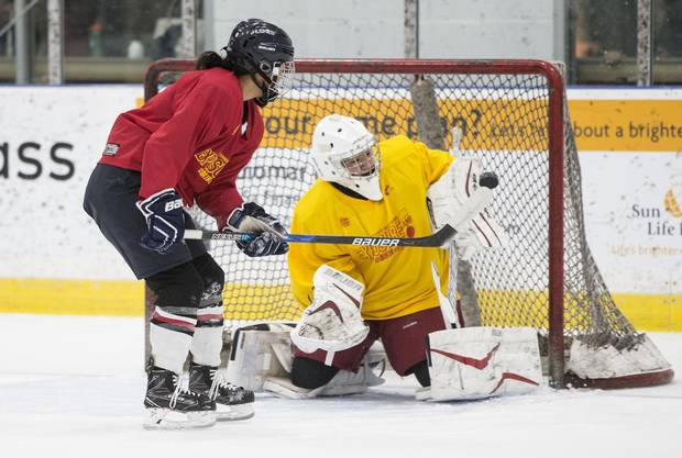 Leah Lum (left) tips a shot past goaltender Emily Yue during a drill.