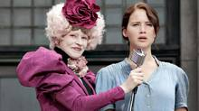 "The coal miner's daughter (Jennifer Lawrence as Katniss Everdeen) and the evil rich person (Elizabeth Banks as Effie Trinket) in a scene from ""The Hunger Games"" (Murray Close/AP)"