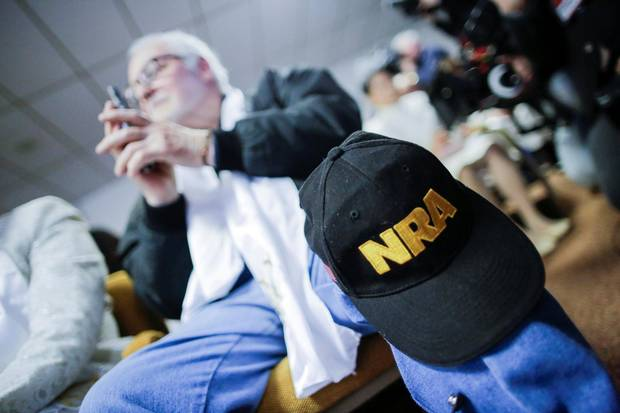 A man with a NRA cap holds his gun while people pray during a blessing ceremony at the Sanctuary Church in Newfoundland, Pa., on Wednesday.