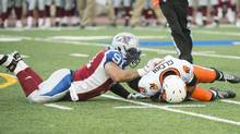 B.C. Lions' quarterback Kevin Glenn, right, is sacked by Montreal Alouettes' Alan-Michael Cash (91) during first half CFL football action in Montreal, Friday, July 4, 2014. (The Canadian Press)