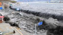 In this March 11, 2011 file photo, a tsunami floods over the breakwater protecting the coastal city of Miyako at Heigawa estuary area after northeastern Japan was hit by a powerful earthquake. (Tomohiko Kano/AP)