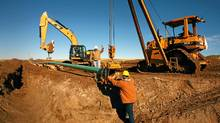 A pipeline crew near Watford City, N.D. Growing oil volumes have fuelled a need for even more pipe. (Matthew Staver/Bloomberg News/Matthew Staver/Bloomberg News)