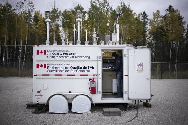 Ryan Abel of the Wood Buffalo Environmental Association checks data at an Environment Canada air quality monitoring station in Fort McKay, Alta., in September 2014.