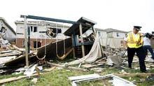 Investigators assess the damage to homes and property in Angus, Ont., on June 18, 2014. Ontario's day of wild weather included a lightning strike that sent four golfers in Stouffville, Ont., to the hospital. (NATHAN DENETTE/THE CANADIAN PRESS)