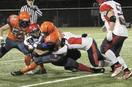 L'Odyssée running back Jérémie Maillet is tackled by Tantramar's MacKenzie Beal and Jory Parsons. L'Odyssée forfeited the game 35-0 after numerous injuries to their players.