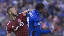 Toronto FC's John Bostock left and Montreal Impact Patrice Bernier battle for the ball during second half MLS action at the Olympic Stadium in Montreal on Saturday March 16, 2013. (Peter McCabe/The Canadian Press)