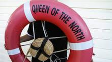 Brandon Clifton holds up a life ring from the Queen of the North in Hartlet Bay, B.C., in August 2006. (John Lehmann/The Globe and Mail)