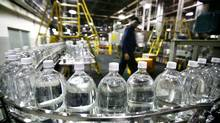 Plastic bottles filled with soda before being labelled are carried on a conveyor belt at Cott's bottling plant in Toronto. (Fernando Morales/The Globe and Mail)