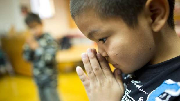 Native children pray at the Chief Matthews School in Masset, B.C. on Oct. 3, 2012 before the start of Haida language class. UBC education professor Dr. Jo-Ann Archibald says there is an important link between culture representation in the classroom and student success. (John Lehmann/The Globe and Mail)