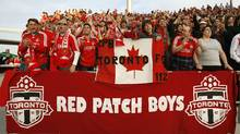 "Toronto FC fan club ""Red Patch Boys"" members cheer on their team during a game against New York at BMO field in Toronto, June 6, 2007. (J.P. MOCZULSKI)"