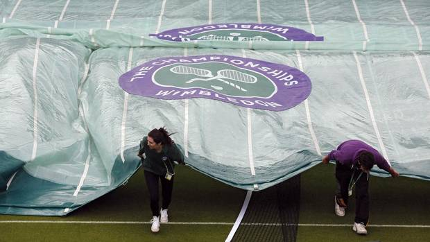 Ground staff pull a rain cover across an outside court, a day before the start of the Wimbledon Tennis Championships in London June 23, 2013. (CHRIS HELGREN/REUTERS)
