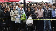 People stand outside the Toronto Eaton Centre shopping mall in Toronto, June 2, 2012 following a fatal shooting. (Mark Blinch/REUTERS)