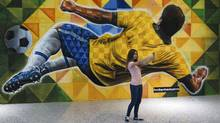 A girl takes a selfie in front of a promotional banner at the Brasilia Juscelino Kubitschek International Airport ahead of the 2014 World Cup, in Brasilia June 11, 2014. (Paul Hanna/REUTERS)