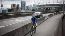 A cyclist passes vehicles driving along the Dunsmuir Street Viaduct adjacent to the Georgia Street Viaduct in Vancouver, June 25, 2013. (Rafal Gerszak for the Globe and Mail)