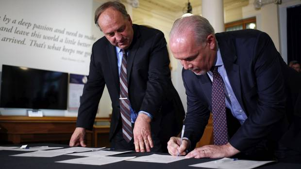 BC Green Leader Andrew Weaver, left, and NDP Leader John Horgan sign an agreement that likely spells the end of Premier Christy Clark's BC Liberal government.