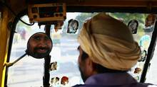 An auto rickshaw driver smiles as he looks in his rear view mirror in New Delhi, India. (Julian Finney/Getty Images)