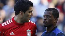 Liverpool's Luis Suarez (L) looks at Manchester United's Patrice Evra (R) during their English Premier League soccer match at Anfield in Liverpool, northern England October 15, 2011. REUTERS/Phil Noble (Phil Noble/Reuters)