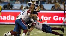 Toronto Argonauts quarterback Jarious Jackson (12) is sacked by Montreal Alouettes defensive end Mike Lockley (91) and linebacker Marc-Olivier Brouillette during first half CFL pre-season action in Toronto on Tuesday June 19, 2012. (Frank Gunn/THE CANADIAN PRESS)