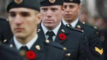 Soldiers wear poppies on their uniforms in a Remembrance Day ceremony in Calgary. (JEFF McINTOSH/THE CANADIAN PRESS)