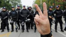 An anti-G20 protester flashes a peace sign near the temporary detention centre in Toronto on June 27, 2010. (Kevin Van Paassen/The Globe and Mail)
