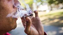 Mathew (last name with held) smokes a joint (also know as Marijuana, weed, grass, pot, chronic, joint, blunt, herb, cannabis, hashish, Mary Jane) at Victory Square in Vancouver's downtown Eastside August 20, 2013. (John Lehmann/The Globe and Mail)