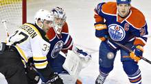 Boston Bruins' Patrice Bergeron, Edmonton Oilers goalie Jason LaBarbera and Oilers' Andrew Ference look for the rebound during second period NHL hockey action in Edmonton on Dec. 12, 2013. (JASON FRANSON/THE CANADIAN PRESS)