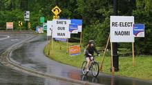 A cyclist passes a series of election signs in North Vancouver on Monday. (Jeff Vinnick For The Globe and Mail)