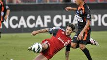Toronto FC's Torsten Frings clears a ball away from Club Deportivo Aguila's Osael Romero (R) during the first half of their CONCACAF Champions League soccer match in Toronto August 1, 2012. (MIKE CASSESE/REUTERS)