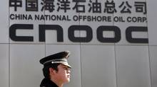A security officer keeps watch outside the headquarters of China National Offshore Oil Corp (CNOOC) in Beijing in this file photo. (CLARO CORTES IV/REUTERS)
