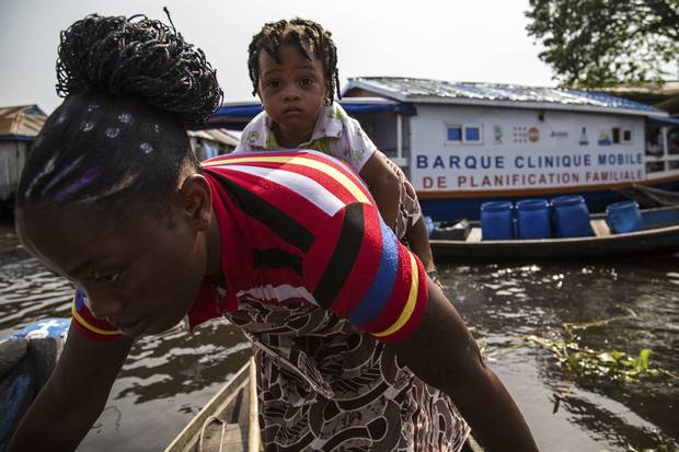 Flavienne San and her daughter Ana head home from contraception boat, nicknamed the Barque Mobile, in So-Ava, Benin. The boat and its crew travel from village to village in a lagoon in southern Benin to spread information about family planning.