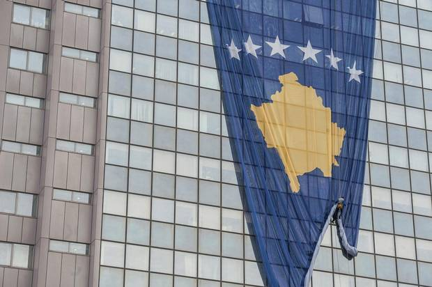 A Kosovo flag hangs outside a government building in Prishtina on Wednesday. Kosovo, which celebrates the 10th anniversary of its split from Serbia on Saturday, continues to struggle to impose a national identity.