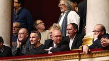 Walter Broccoli, top right, an ArcelorMittal worker from the Florange site and labour union representative, listens with colleagues to questions about the plant's future at the National Assembly in Paris Nov. 28, 2012. (CHARLES PLATIAU/Reuters)