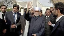 Pakistani cleric Tahir-ul-Qadri, centre, heads to Lahore on June 23 following this week's fatal raid in Punjab. (Anjum Naveed/The Associated Press)
