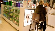 Beauty adviser Jennifer McKnight, right, helps a customer at one of the open cosmetics displays at Sears in Mississauga, Ont. (Peter Power/Peter Power/THE GLOBE AND MAIL)