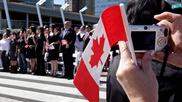 A woman takes a photograph at a citizenship ceremony in Vancouver on July 1, 2009.