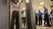 A Transportation Security Administration instructor stands in a full-body scanner as security officers learn how to run the device at the Salt Lake City airport in March of 2009.