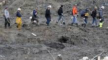 A line of rescue workers arrives to look for victims in the mudslide near Oso, Washington as efforts continued to locate victims March 26, 2014. The death toll from a massive landslide in Washington state stood at 24 on Wednesday, but the mud-stricken community braced for a higher body count as search teams combed through debris looking for scores of people still missing four days after the disaster. (RICK WILKING/REUTERS)
