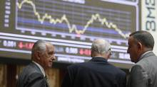 Traders look at electronic boards at the stock exchange in Madrid June 12, 2012. (ANDREA COMAS/REUTERS)