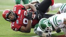 Calgary Stampeders' Nik Lewis, left, is tackled by Saskatchewan Roughriders' Macho Harris during first half CFL Western semi-final football action in Calgary, Alberta on Sunday, Nov. 11, 2012. (Larry MacDougal/THE CANADIAN PRESS)